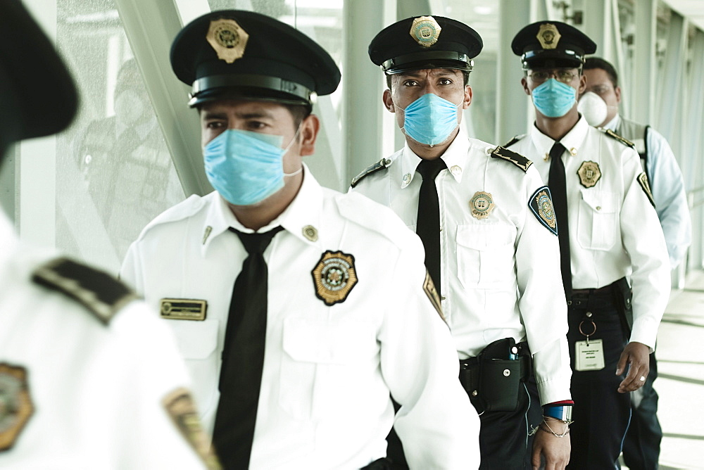 Policemen walking at the airport wearing blue masks. Mexico city, DF, Mexico.
