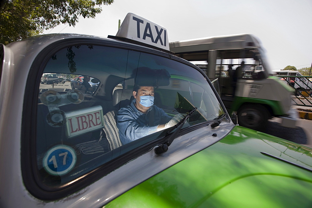 A taxi driver wears mask and plastic gloves inside his cab in Mexico City, DF, Mexico.