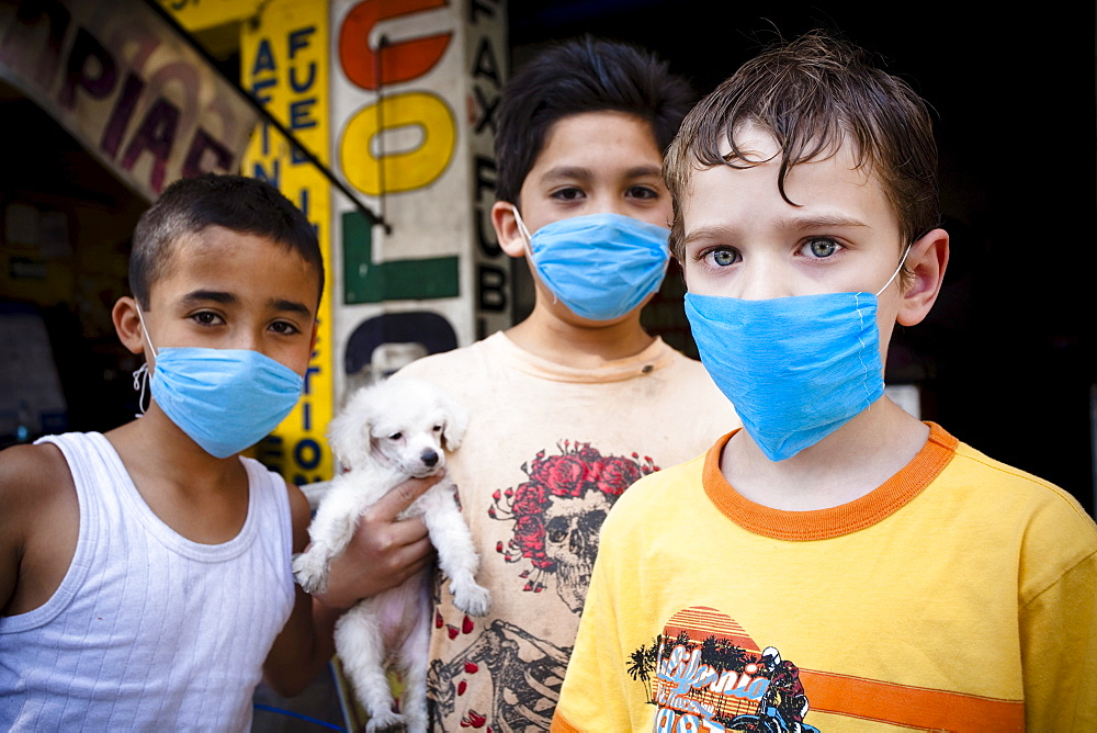 Portrait of three kids wearing masks  holding a small puppy in the street during the swine flu epidemic in Mexico city, DF, Mexi