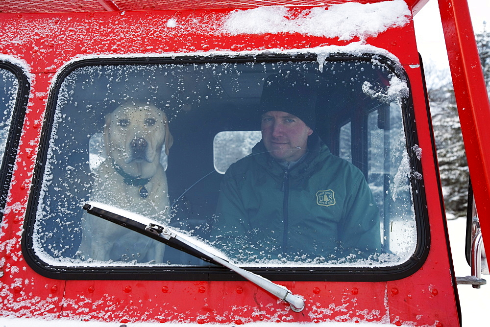 Lead Snow Ranger with his avalanche rescue dog in a snow cat.