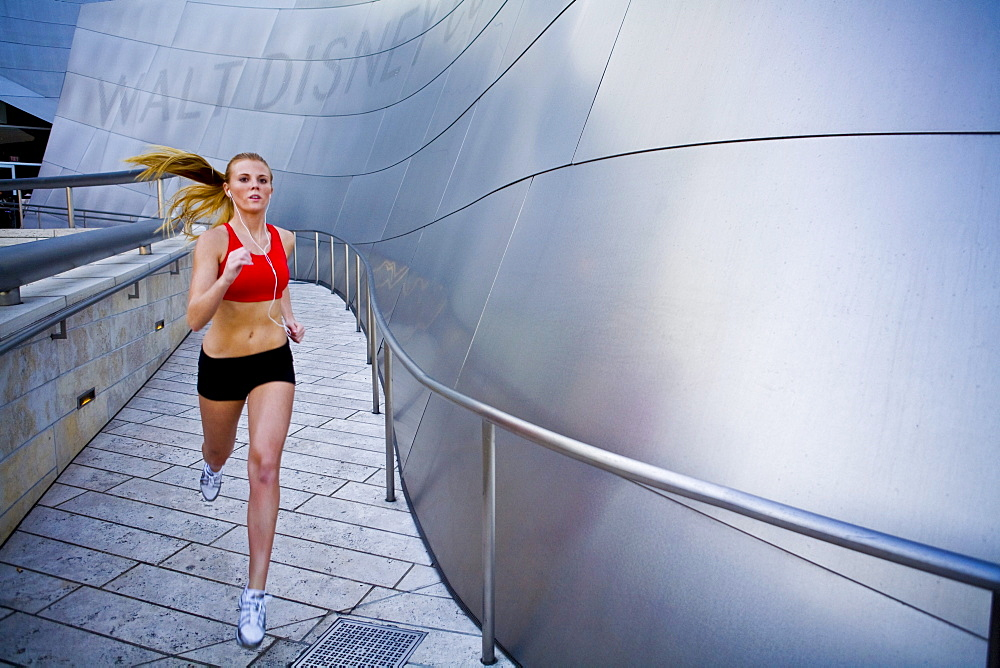 A young, athletic woman runs beside a concert hall in LA, while listening to headphones.