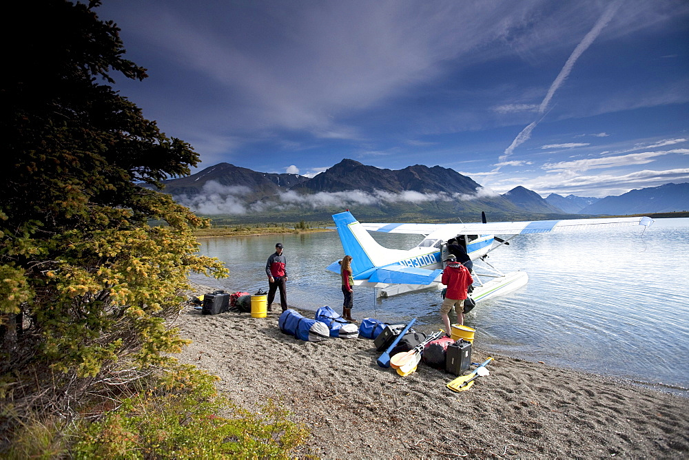 Two men and one woman unload gear from a plane on a lake in Alaska.