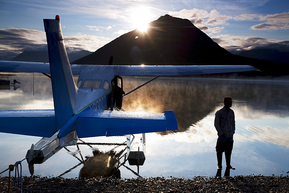 A man stands next to a float plane in Twin Lakes in Lake Clark National Park, Alaska.