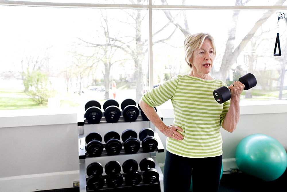 Older woman exercising in a gym.