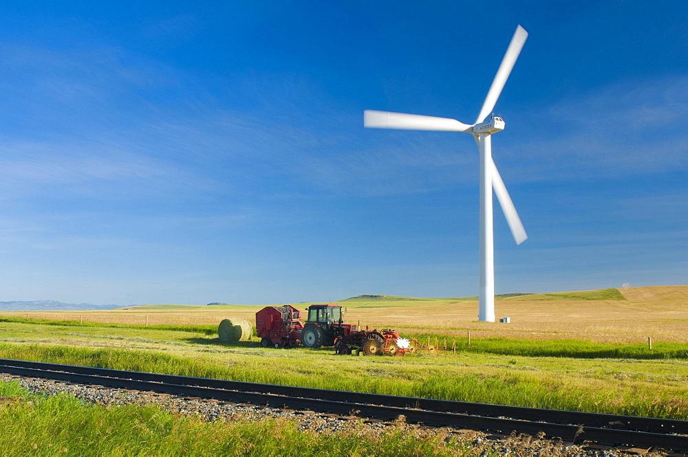 A single windmill spins over a framer's field alongside and old tractor. (blurred motion)