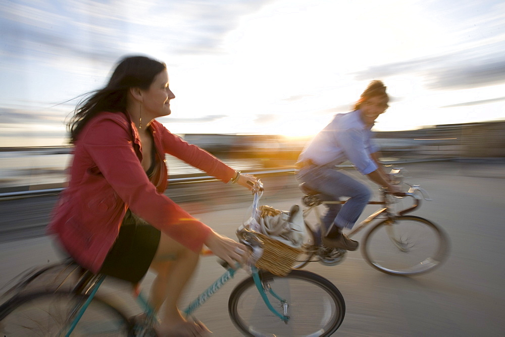 A young man and woman smile as they enjoy a sunny afternoon bike ride through an open street in Portland, ME. (Motion Blur)