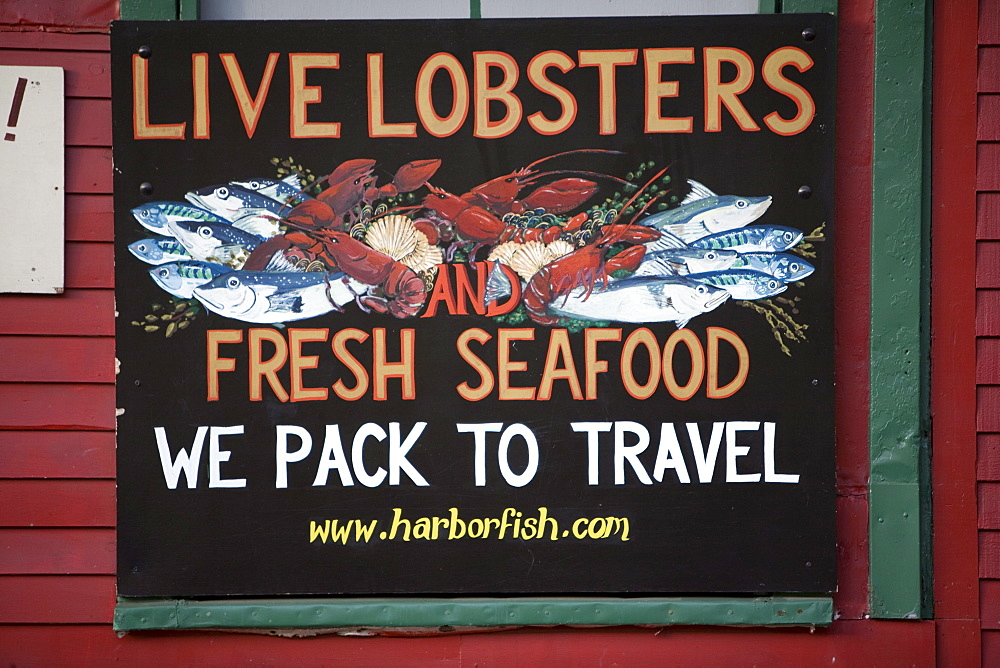A colorfully painted sign advertising live lobsters and fresh seafood hangs on a red wooden wall in Portland, ME.