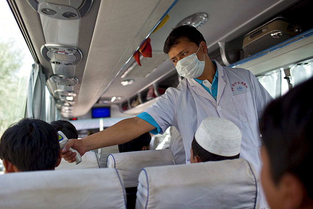 Testing for the H1N1 virus on a bus near Khotan, Xinjiang, China.