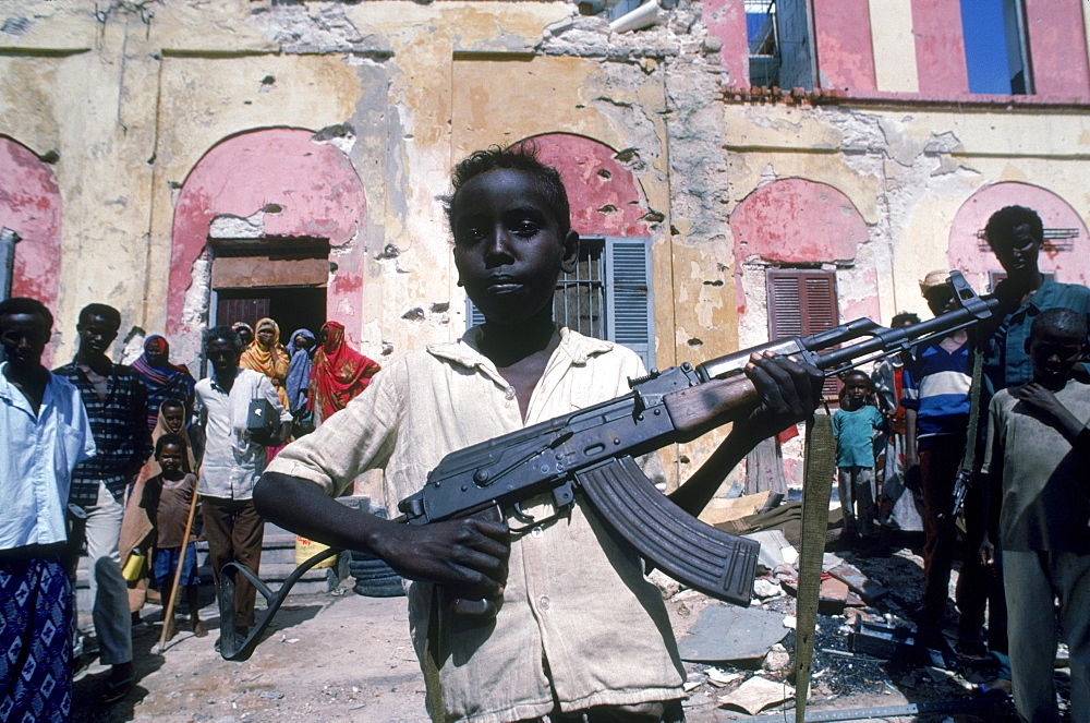Young boy shows a gun in front of bullet riddled building in Mogadishu, Somalia.