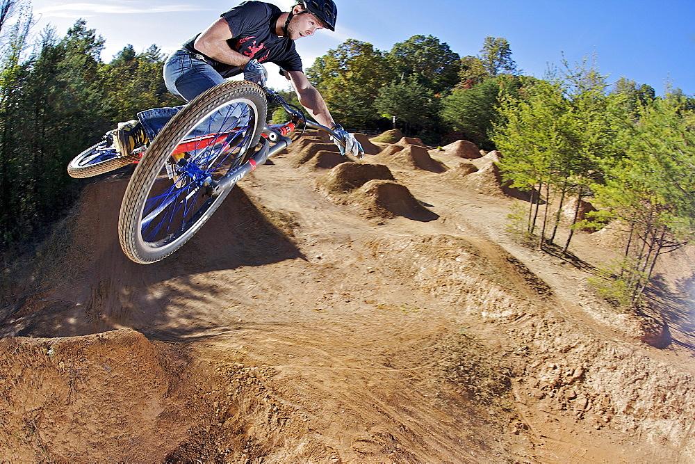 A man flying through the air on a mountain bike.