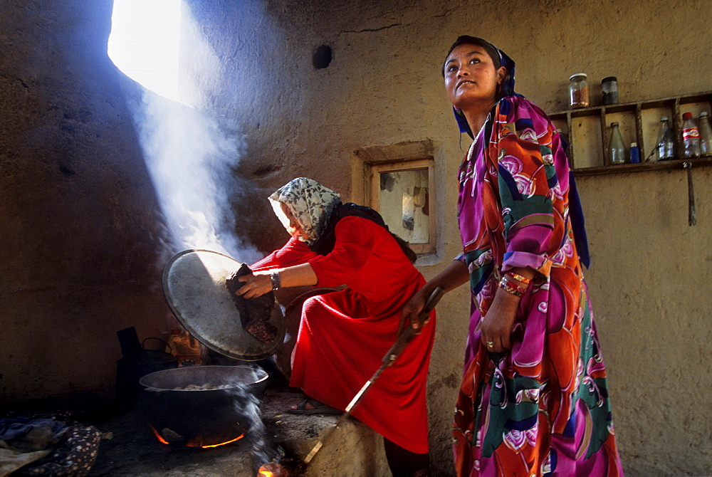 Women cook over an open fire in the kitchen area of a traditional northern Afghan home on the outskirts of Mazar-i Sharif, Afghanistan - 857-55489