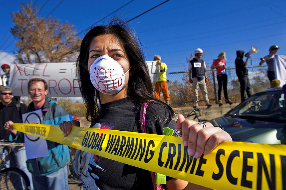 A woman in a mask holds onto a sign during a rally outside of a coal plant that was protesting against coal power and for raising awareness of global warming, on the international day of action promoted by 350.org, October 24, 2009, in Boulder, Colorado