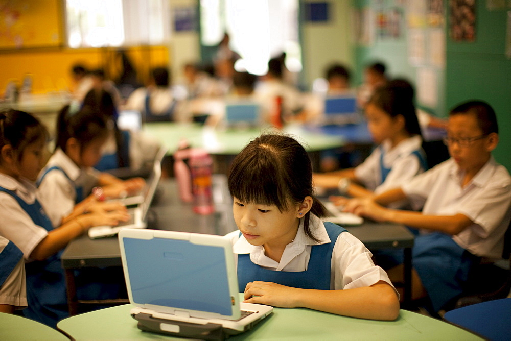 Schoolchildren in 3rd grade at the Canberra Public Primary School use laptops during a summer vacation enrichment class in English.