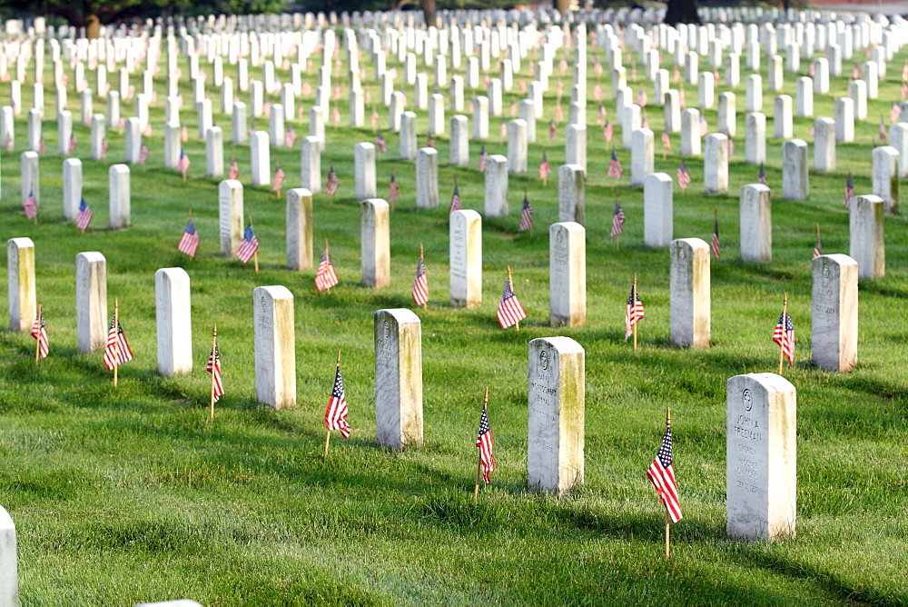 Soldiers place flags on graves at Arlington National Cemetery.