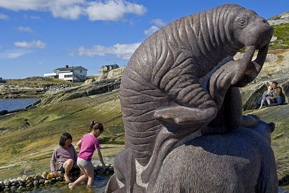 Children play in the water around a statue on a sunny day in Nuuk, Greenland.