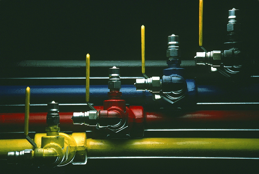 Four pipes carrying red, blue, yellow and black colors during printing process at plant in Dallas, TX.