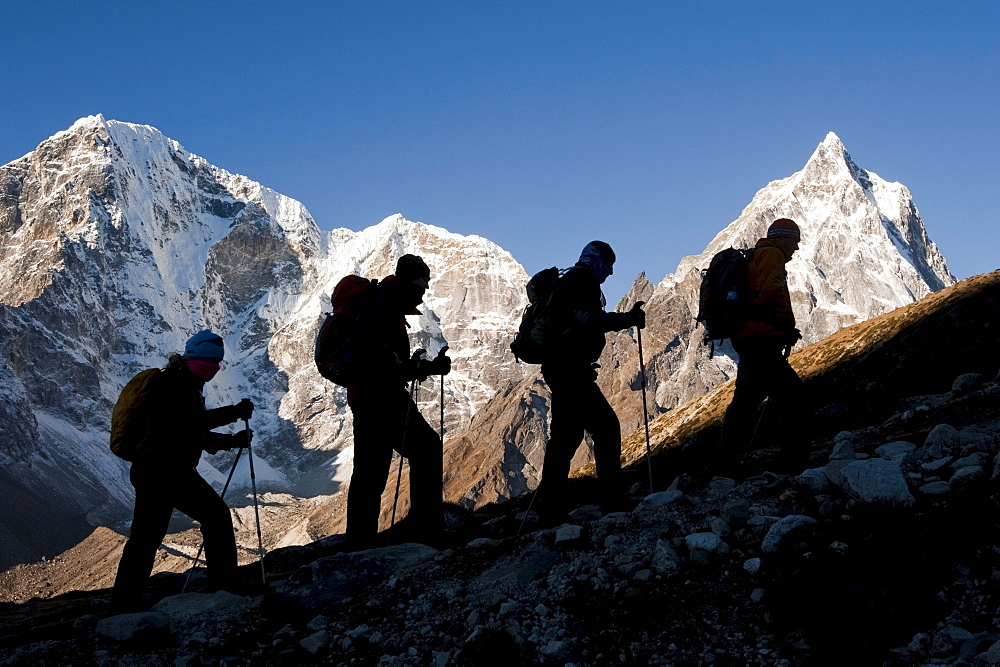 Hikers silhouetted against a sunrise mountain backdrop above Dhugla, 16,000ft.-trek to mt. everest base camp.