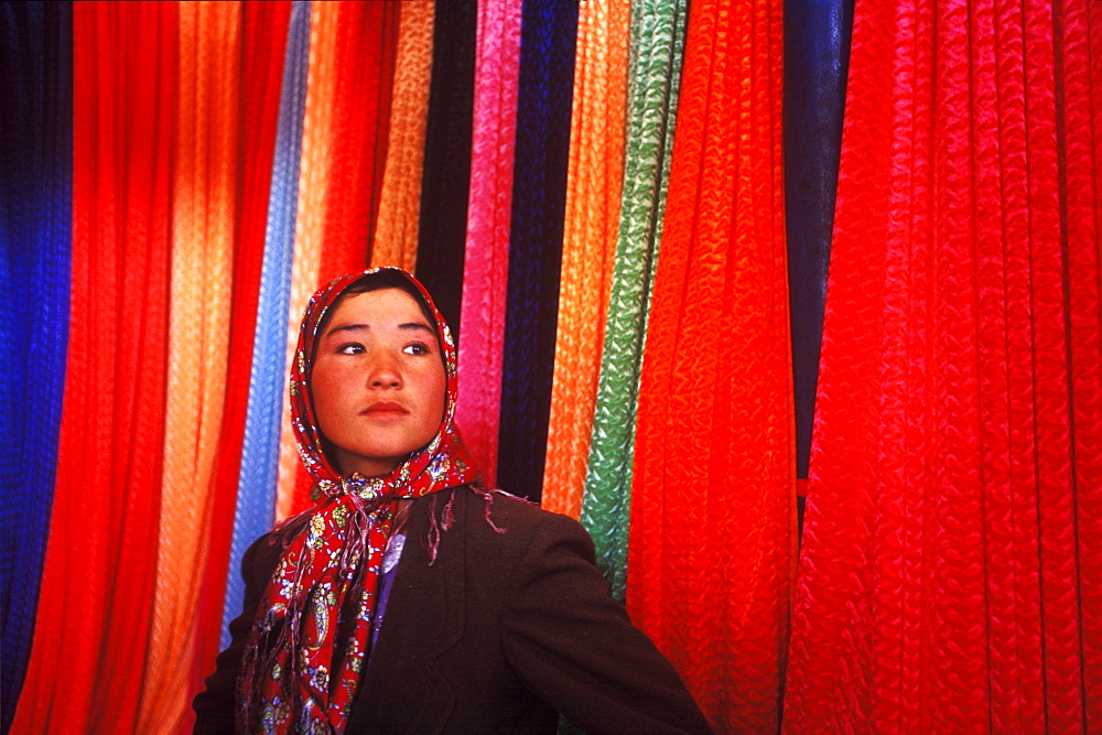 A young woman stands in a fabric stall in a market in Kashgar, China.