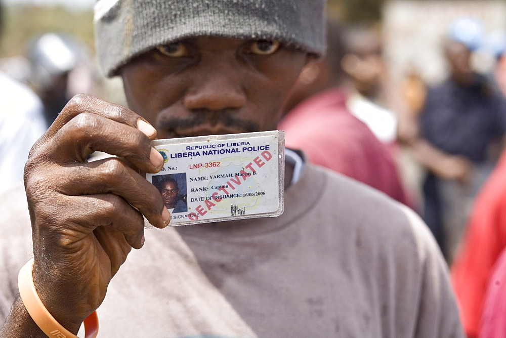 Young man holding up his deactivated Police ID card. Former members of the Armed forces of Liberia and Liberian Nation Police block the road at EWA junctions demanding the President pay back payments for the years they were not paid under the Taylor regime. The protest ended in violence with tear gas being firied on the crowd.