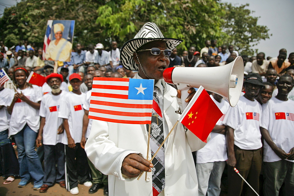 Liberians line the streets of Monrovia, Liberia to celebrate Chinese President Hu's visit. Besides rebuilding the National football stadium Chinese aid to the war torn nations is very popular with the locals. Liberia is rich in iron ore, timber, rubber and other resources which are desired by China.