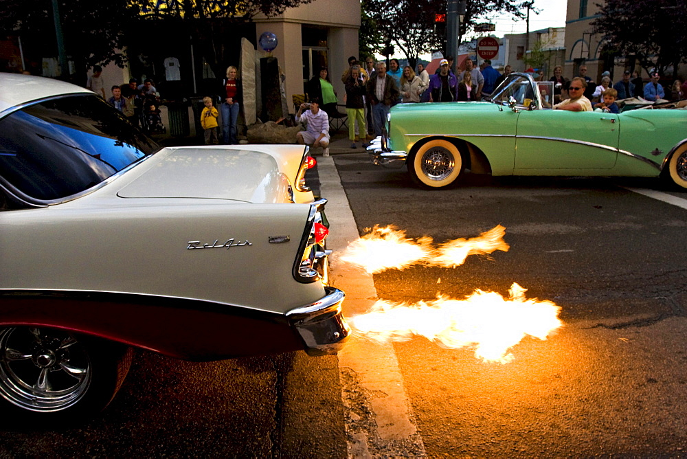 Spectators stand along a street watching a vintage car with a flaming exhaust in Coeur d'Alene, Idaho.