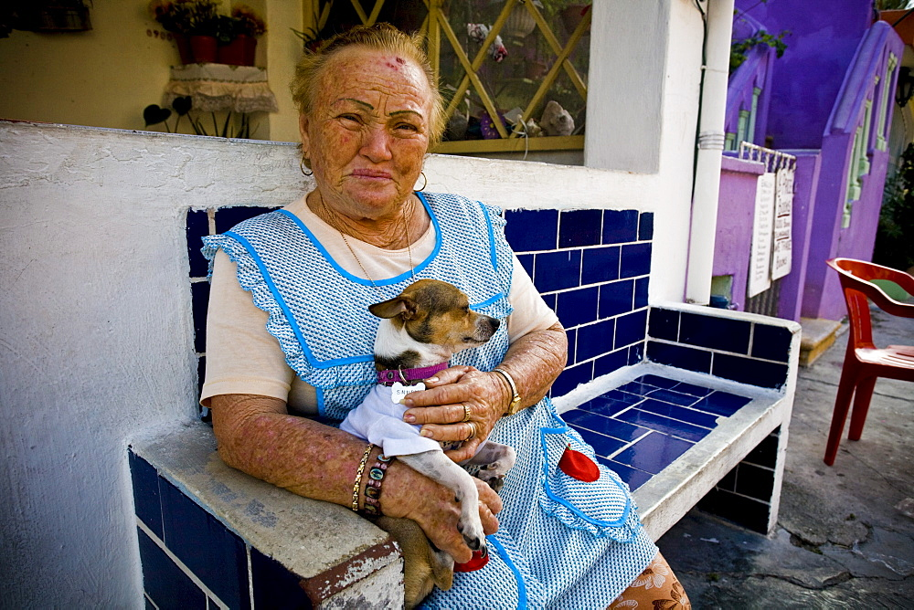 Portrait of a woman posing with her dog on her lap on Isla Mujeres, Mexico.