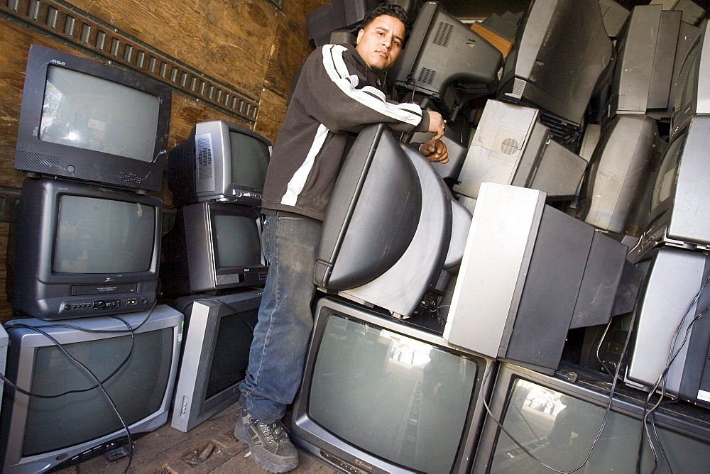 At CRT Recycling in Brockton, Massachusetts, German Pantoja stands with TVs that he selected and are put in a sea container for shipment to Venezuela, where they will be repaired and sold as used TVs.