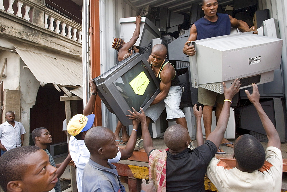 Workers unload televisions at the Alaba Market, Lagos Nigeria. Many of the electronics here are second hand and shipped from Asia, the USA or Europe for reuse. The small shop dealers buy electronics from the containers and are very good at repairing the goods for sale. Only when material has no value is it sent to nearby dumps.