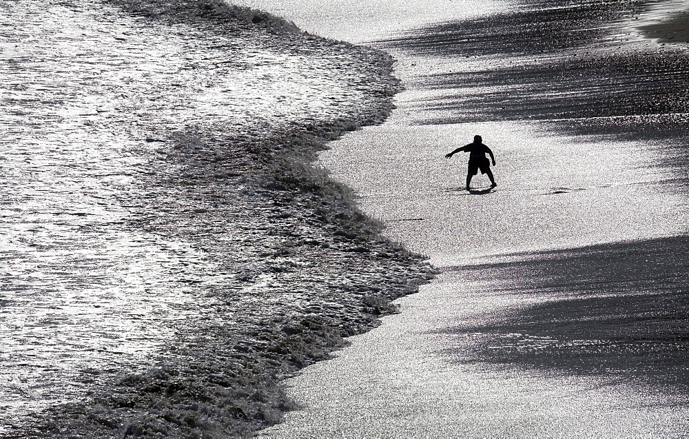 The surf and wet sand of San Simeon Beach, California, create a uniquely looking playground for one young man.