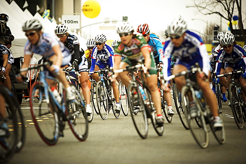 Front view of a pack of female bicycle racers in the Amgen Tour of California, downtown Santa Rosa, California.