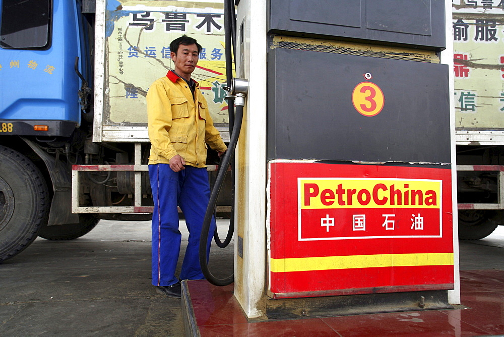 A gas station attendant at a PetroChina station pumps fuel in to a truck in Tazhong in China's western Xinjiang Province.