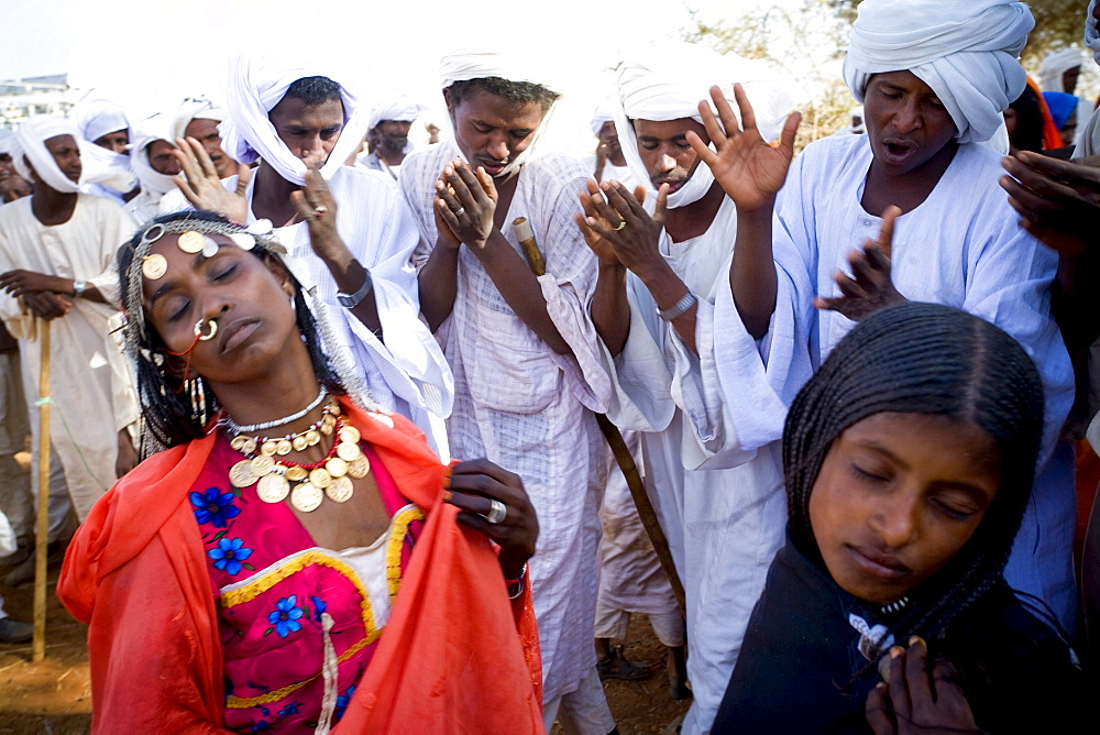 Shanabla men dance and chant at a wedding celebration near El Obeid, Sudan. A nomadic tribe they raise camels.