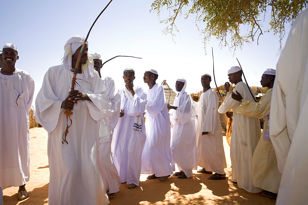 Young men of the Darhammid tribe dance in the  village of Limrat, Sudan during a wedding celebration. They raise camels.
