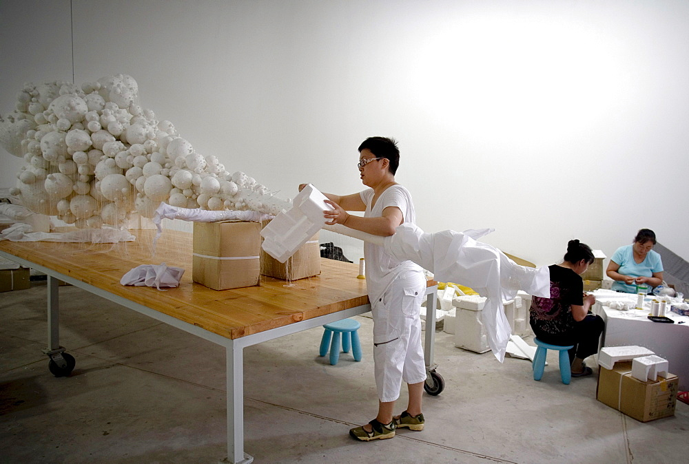 """Chinese artist Lin Tianmiao works on the sculpture """"Mothers !!! no. 14""""  in her studio in Songzhuang Village, east of Beijing."""