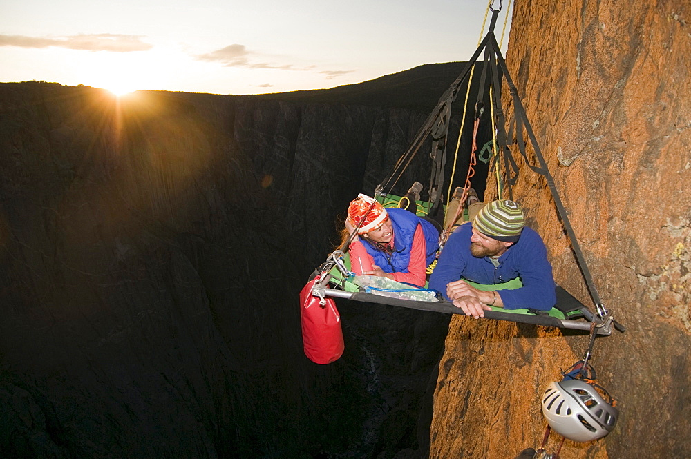 A man and woman on a portaledge at sunset while rock climbing a vertical face in Gunnison, Colorado.