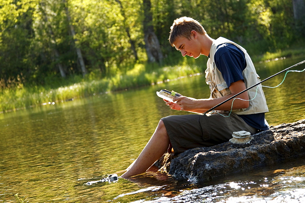 A teenage boy sits on a rock as he chooses a fly while fly fishing on the Swan River near Bigfork, Montana.
