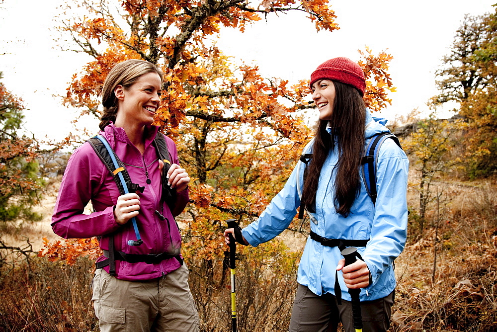 Two young women laughing together while out hiking in the Columbia River Gorge, Oregon.