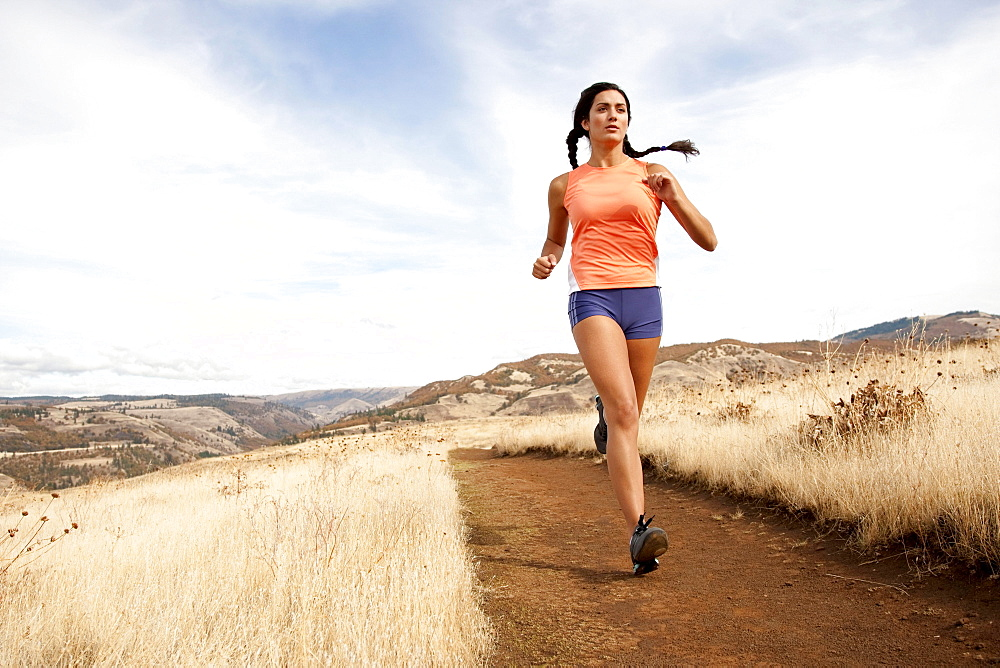 An athletic female jogs on a  dirt trail on an autumn day.
