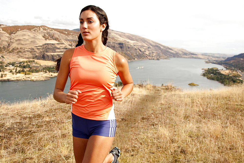 An athletic female jogs on a  dirt trail on an autumn day with the Columbia River Gorge in the distance.