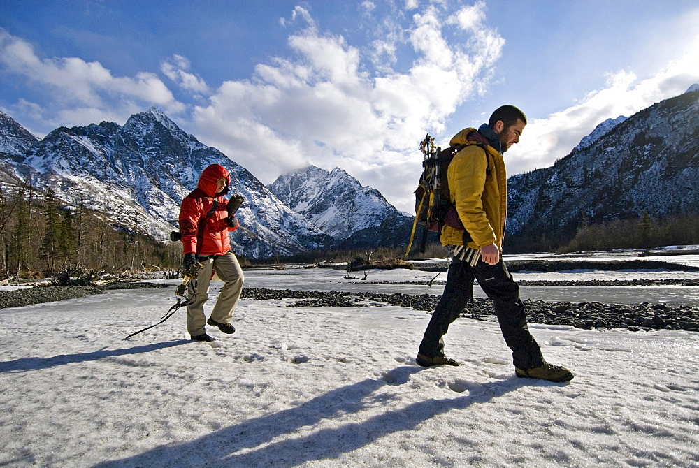 Two young ice climbers walk across a snowy river, with gear in hand, on their way to an afternoon ice climb in Echo Bend, Alaska.