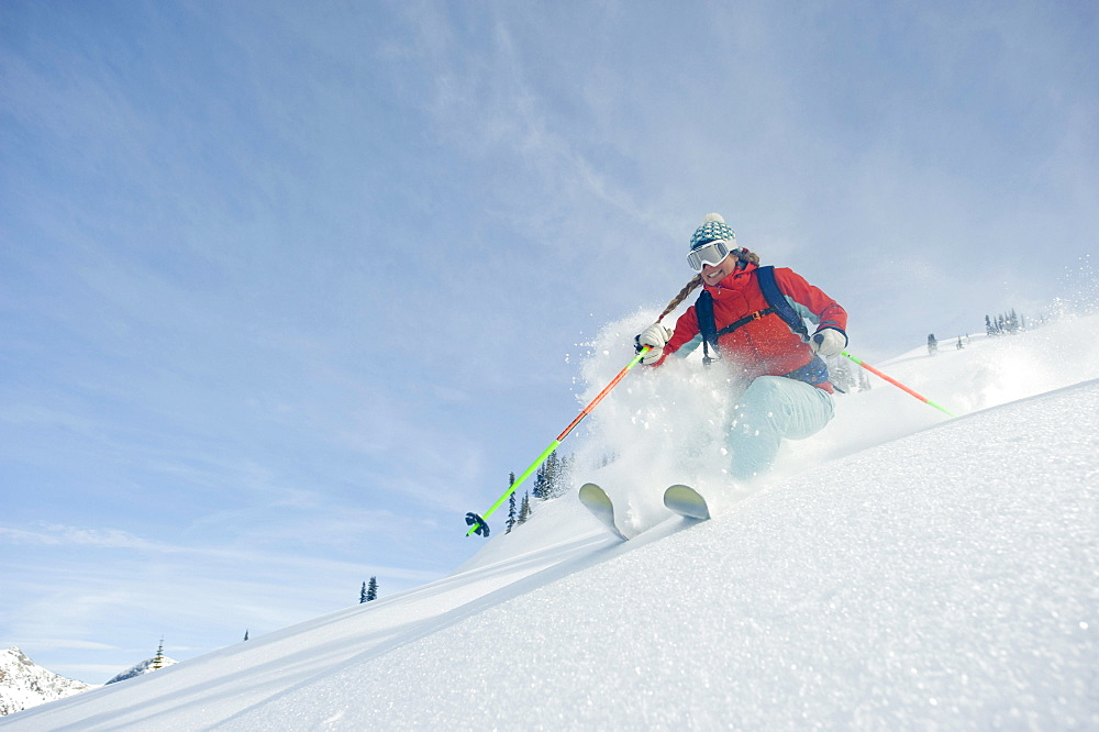 A woman skier smiles as she skis the powder in the backcountry of the Selkirk Mountains, Canada.