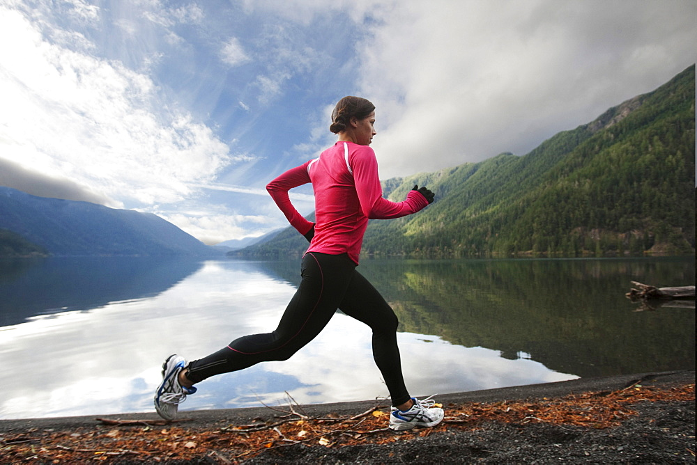 A female jogging along the Lake Crescent shore.