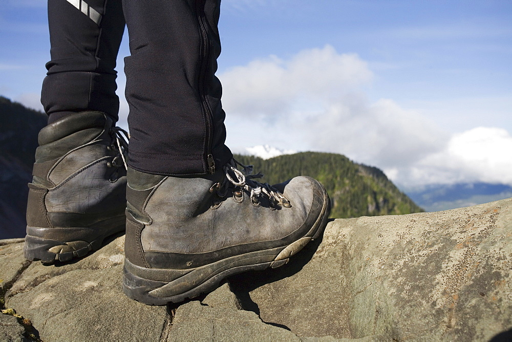 A low shot of a backpacker's lower legs and boots, standing on granite with forested mountains in the background.