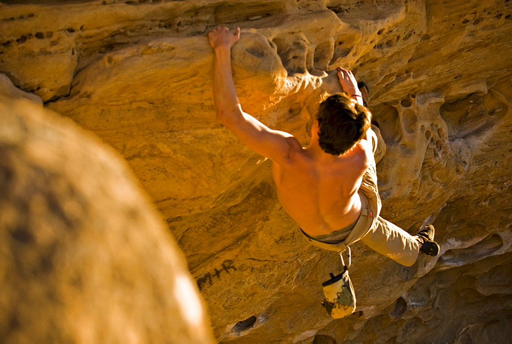 A young man rock climbs a boulder problem in Santa Barbara, CA.