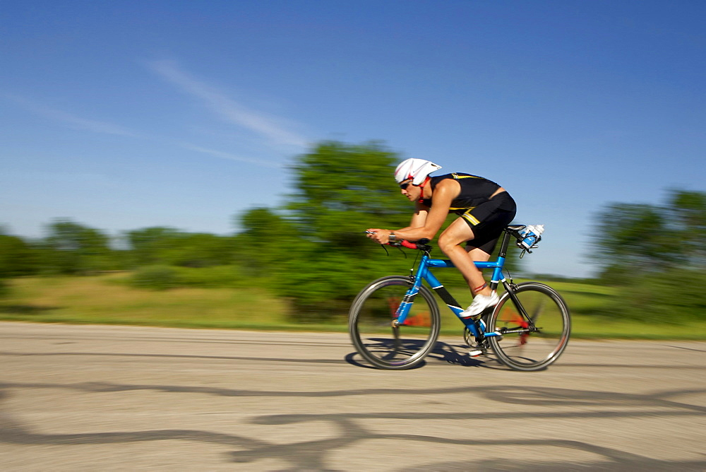 A male athelete training for a triathlon at a lake on a bike.