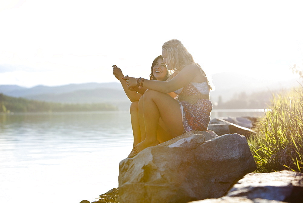 Two young women laugh while texting at sunset on the lake.