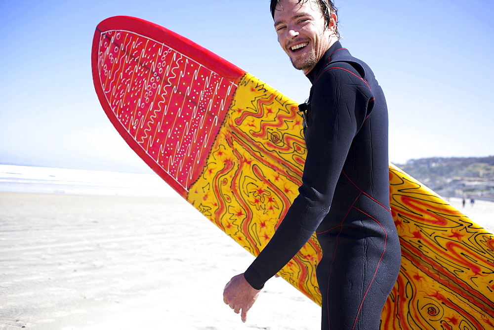Male surfer runs towards the water while smiling.