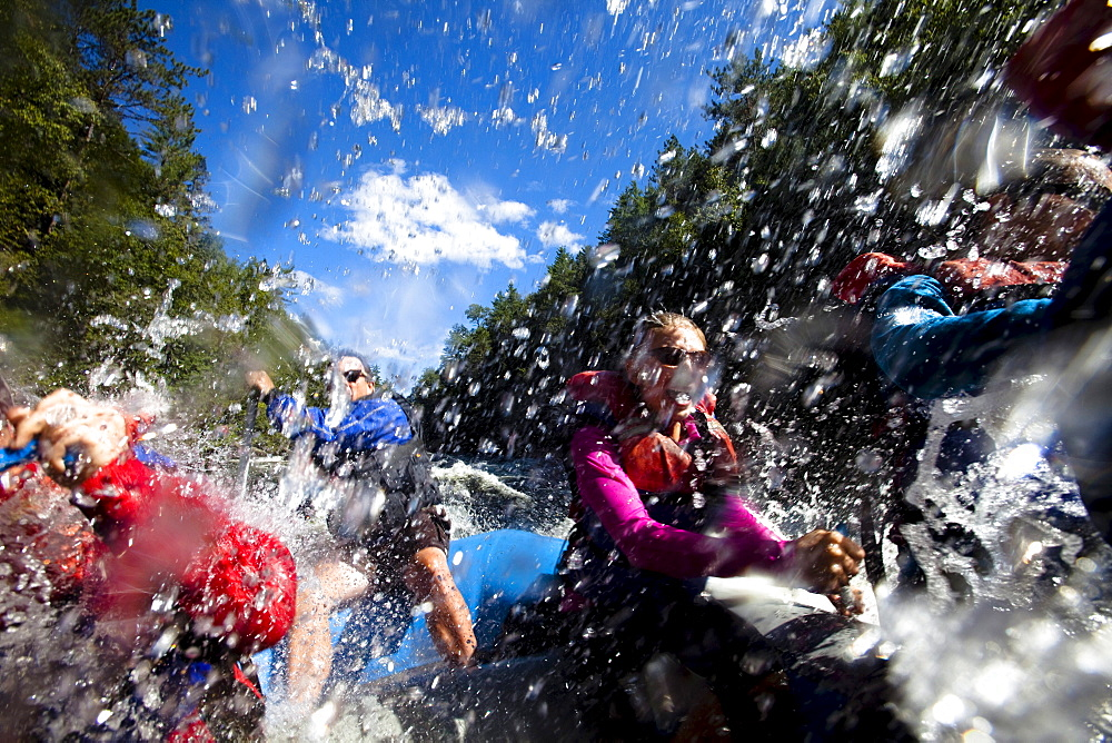 A group of adults whitewater rafting in Maine.