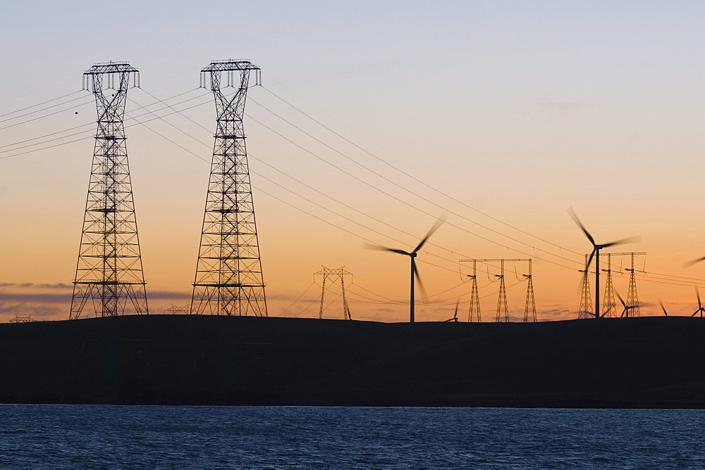 Wind turbines and power transmission lines at sunset near San Francisco
