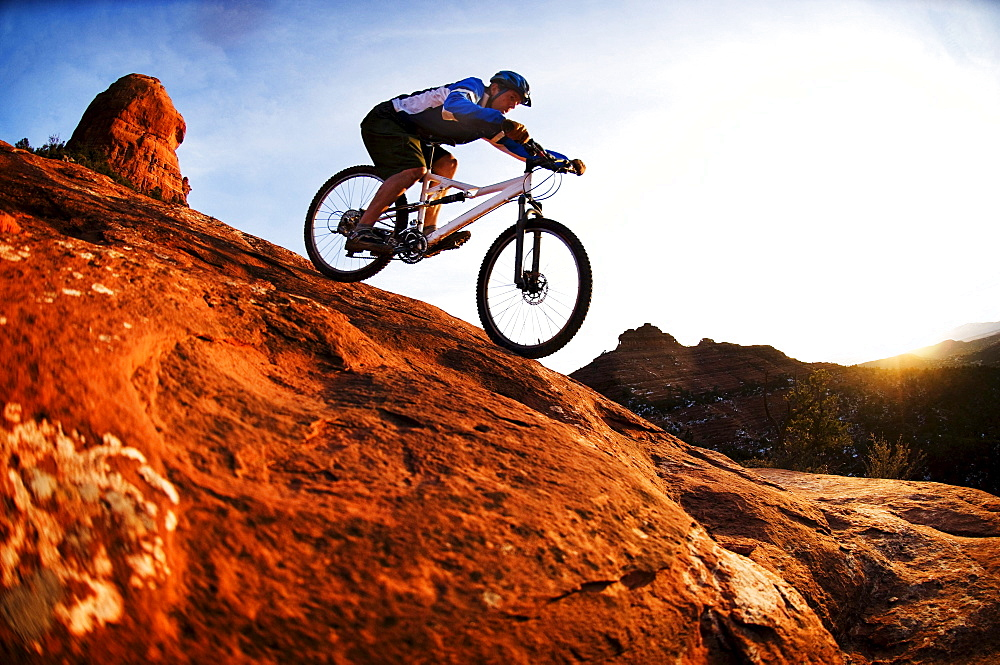 A middle age man rides his mountain bike through the red rock country around Sedona, Az at sunset. - 857-78671